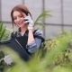 Florist Talking On The Phone In Greenhouse