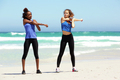 Two young women stretching exercise at the beach