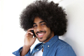 Smiling young man with afro using cellphone