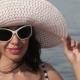 Beautiful Woman In Sunglasses And Big Hat Enjoying On Sea