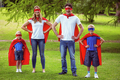 Happy family pretending to be superhero in the park