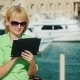 A Female Tourist Enjoys The Tablet Against The Backdrop Of The Bay With Yachts