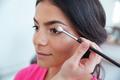 Makeup artist applying eyeshadow to attractive woman