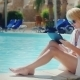 Woman Relaxing By The Pool, Enjoying The Tablet
