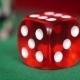 Red Dice Rotation And Casino Chips On Green Felt