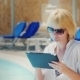 Woman In Sunglasses Enjoys The Tablet Pool