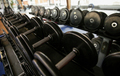 close up of dumbbells and sports equipment in gym