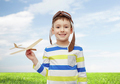 happy little boy in aviator hat with airplane