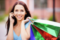 Young smiling woman to purchases and telephone.