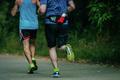 two athletes run through the Park