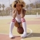 Attractive Young Woman Sitting On a Basketball