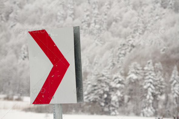 Traffic sign in front of the forest under snow - Stock Photo - Images