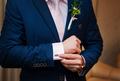 Hands of wedding groom in a white shirt dress cufflinks