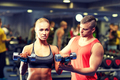 young couple with dumbbells flexing muscles in gym