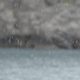 Rain On Calm Sea With Rocks In Background