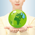 close up of woman holding green globe in her hands