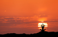 Sunset landscape with girl practicing yoga on the hill