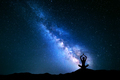 Milky Way and silhouette of a girl practicing yoga