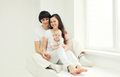 Happy family, mother and father with baby home in white room nea