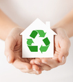 hands holding house with green recycling sign