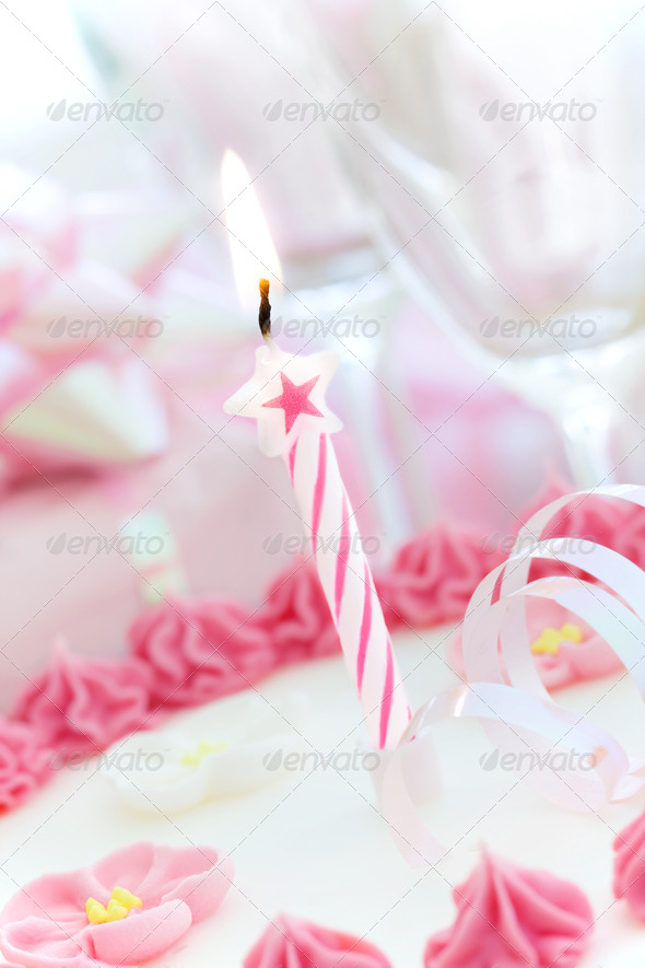 Pink and white birthday cake decorated with a single candle