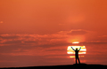 Sunset landscape with silhouette of a man with raised-up arms