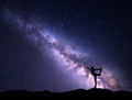 Milky Way. Night sky and silhouette of a happy girl