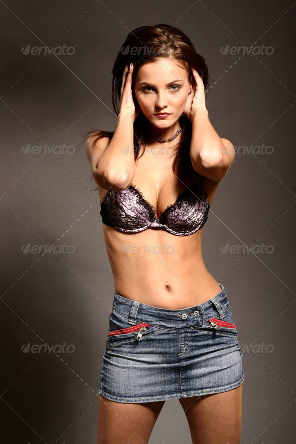 Sexy woman posing in jeans skirt by gray background - Stock Photo - Images