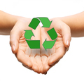 close up of hands holding green recycling sign