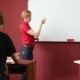 Female Teacher Giving a Lecture At The University. Transmits Notebook