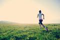Runner athlete running on grass seaside