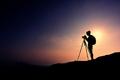 Female photographer on sunset mountain peak