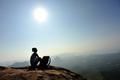 Female backpacker sitting on mountain peak