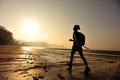 Woman hiking on sunrise beach