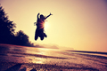 young woman jumping on sunrise beach
