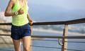 fitness sports woman running on wooden boardwalk seaside