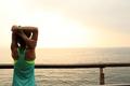 fitness sports woman runner stretching on wooden boardwalk seaside