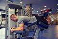 man flexing leg muscles on gym machine
