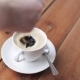 Hand Dropping Sugar Into Coffee Cup On Table 40