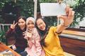 Friendly girls making selfie in cafe