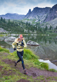 Trail running woman cross country in mountains on summer beautiful day