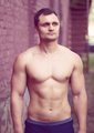 Young man athlete bodybuilder looks into the distance street workout outdoors in the summer