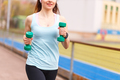 Young smiling woman jogging with dumbbells