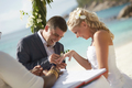 Couple exchanging rings during wedding registry ceremony on trop