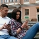 Beautiful Young Woman Using Phone And Talking To Young Man While Sitting On a Bench In a Park