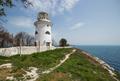 Beautiful old white lighthouse on the sea coastline. Summer seascape