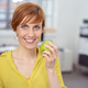 Healthy smiling woman holding a fresh green apple