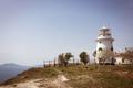Beautiful old white lighthouse on the sea coastline. Summer seascape.