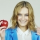 Girl With Red Apple In His Hand Showing Approval Gesture With Thumb Up