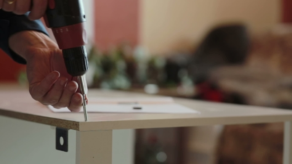 Download Man Assembles Furniture Using a Power Screwdriver nulled download